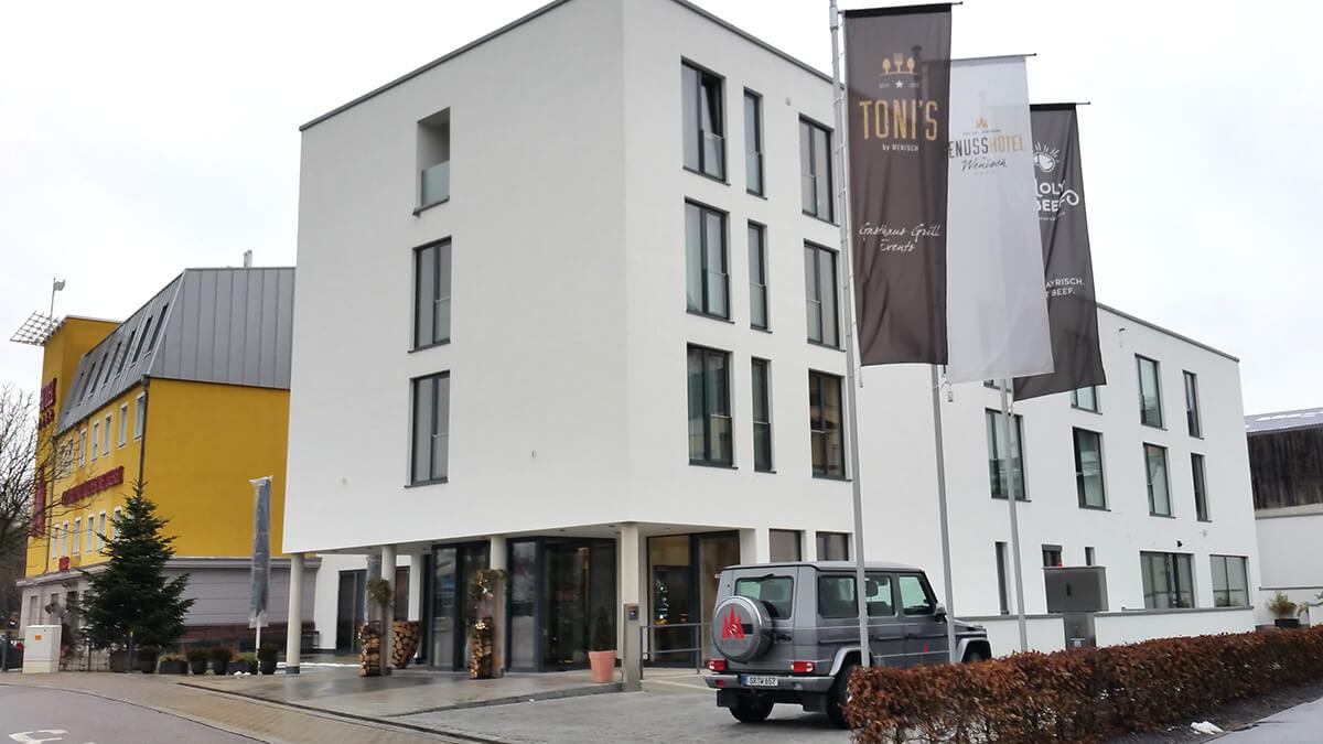 Außenansicht eines Hotels mit Restaurant und Parkplatz mit Fahnen