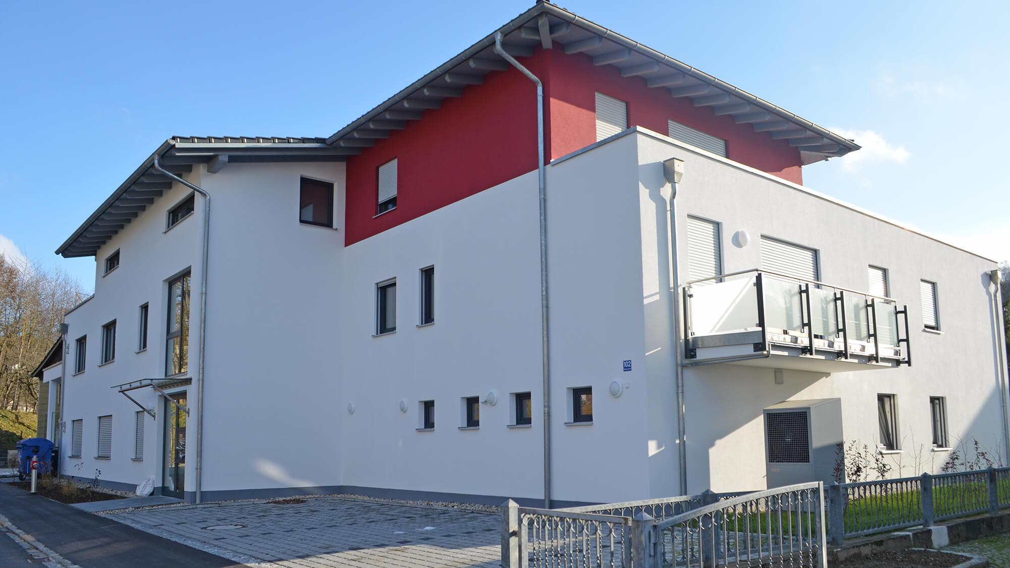 Außenansicht eines Wohnhauses mit Balkon und Doppelgaragen