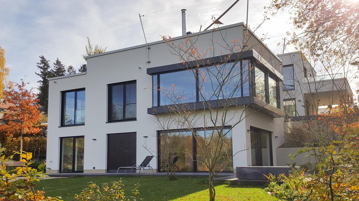Modernes Haus mit vielen Fenstern und Garten