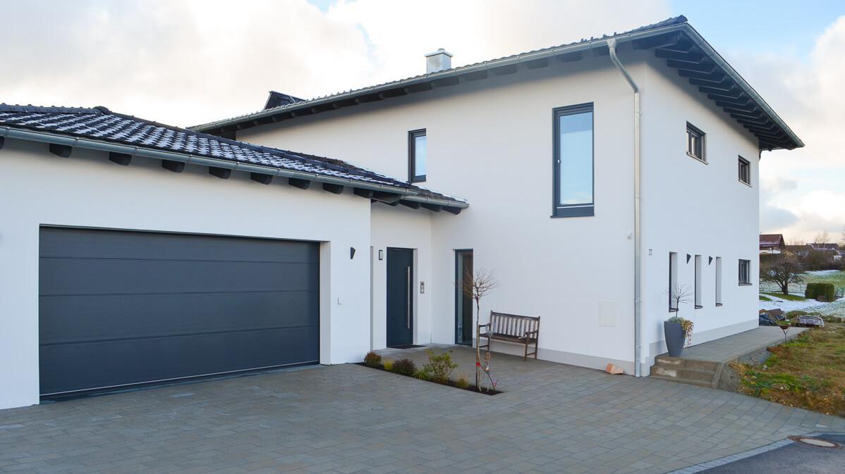 Modernes Wohnhaus mit Garage, Garten und gepflasterter Einfahrt
