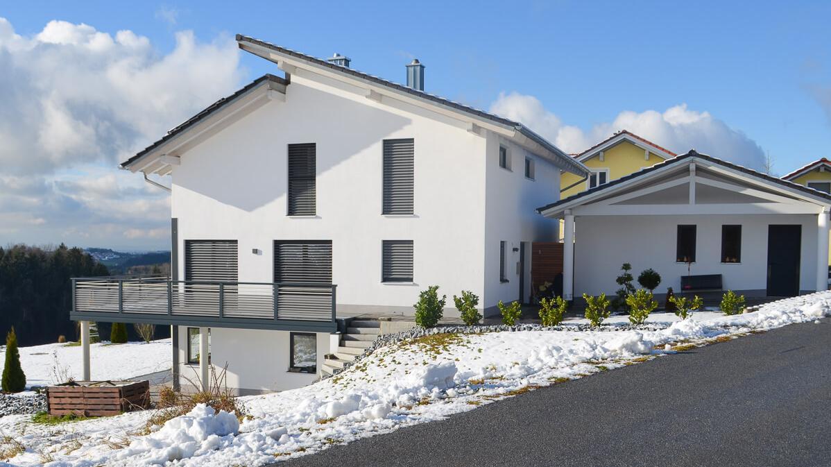 Einfamilienhaus mit verschneiten Garten und abgetrennter Garage