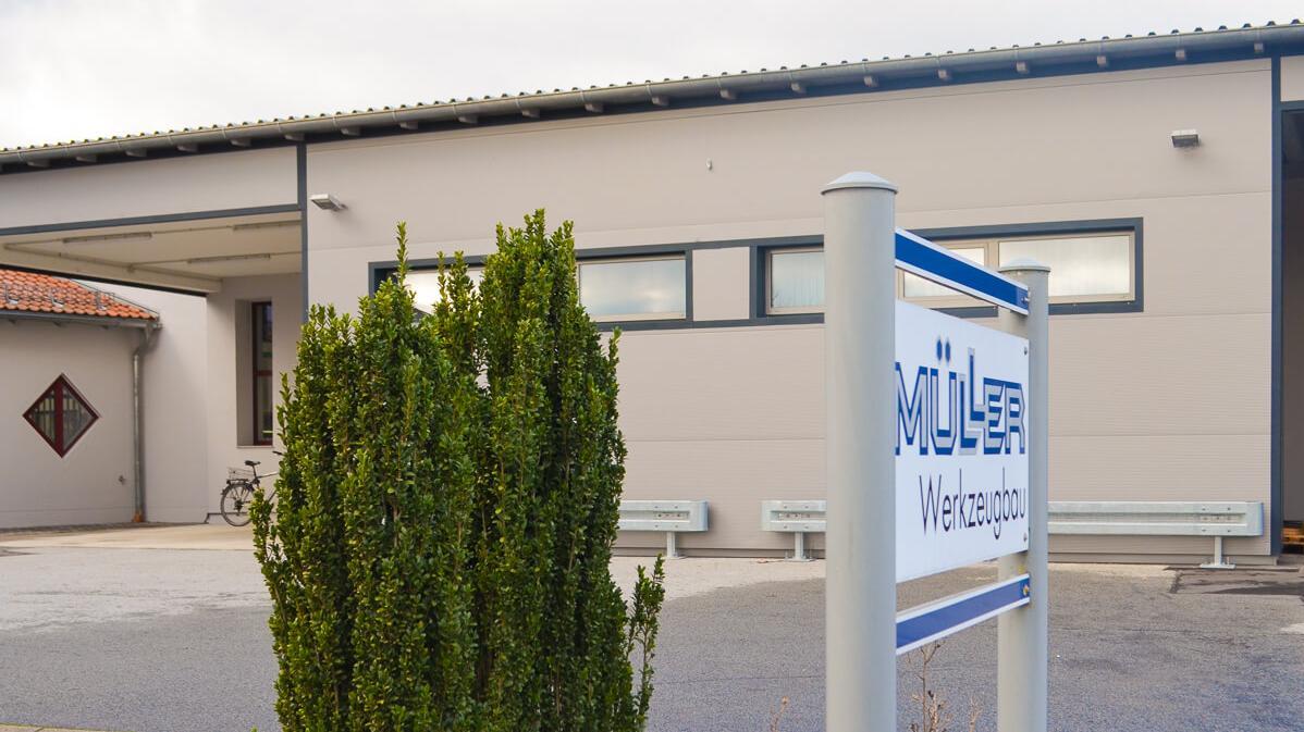 Firmenschild vor der neu errichtetem Produktionshalle