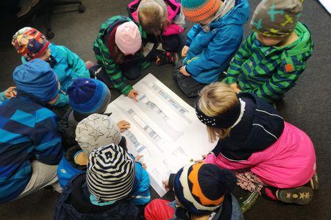 Kinder bilden einen Kreis um einen Bauplan